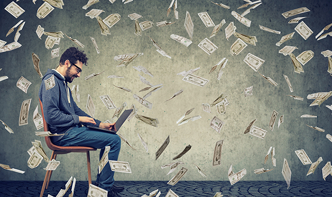 /tech worker surrounded by money flying in the room Copyright_pathdoc-AdobeStock