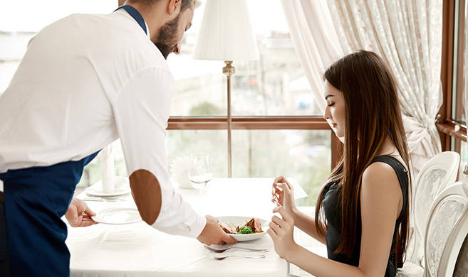 a woman is being served at an elegant restaurant
