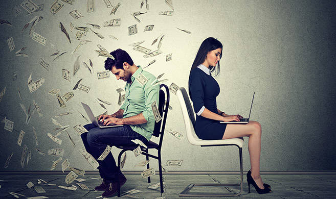 a man and a woman work on a computer, the man has money falling on him