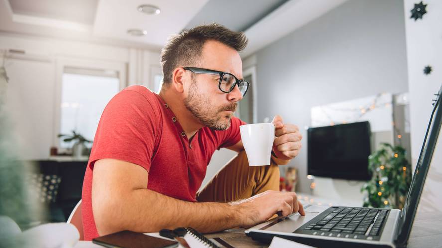 man in a shirt looking at a computer with a coffee in his hand - Adobe Stock