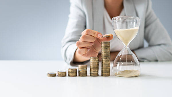 woman in suit adding coins on a pile next to an hourglass - Andrey Popov-AdobeStock