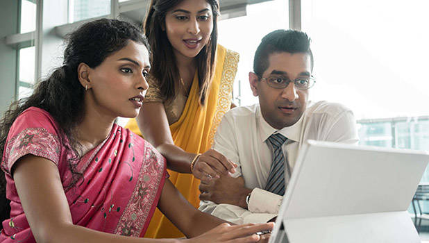 Indian people working together in front of a computer - kzenon - adobe stock