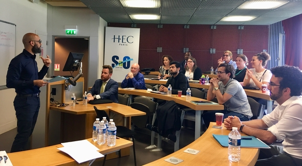 HEC Paris Professor Daniel Martinez and Dane Pflueger talking in a room to researchers