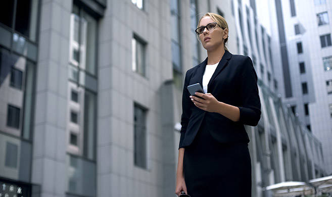a woman in a suit looking at the horizon in the middle of buildings - cover photo