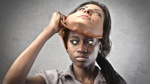 Black woman pulling off a mask depicting a white womans face - Racial prejudice