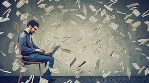 tech worker surrounded by money flying in the room ©pathdoc_AdobeStock