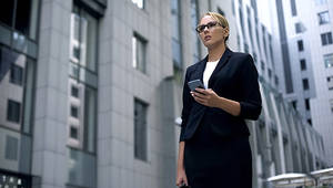 a woman in a suit looking at the horizon in the middle of buildings